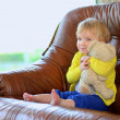 Little girl sitting on sofa holding teddy bear — Stockfoto #46835485