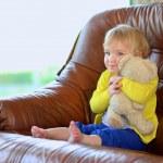 petite fille assise sur le canapé tenant l'ours en peluche — Photo #46835485