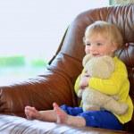 petite fille assise sur le canapé tenant l'ours en peluche — Photo #46835491