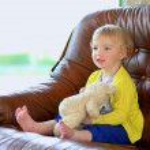 Little girl sitting on sofa holding teddy bear — Stock Photo #46835497