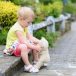 Cute little girl playing with teddy bear on the street — Stock Photo #46994359