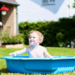 Happy child playing with water in plastic bath in the garden — Stock Photo #46994431
