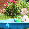 Happy child playing with water in plastic bath in the garden — Stock Photo #46994445