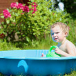 Happy child playing with water in plastic bath in the garden — Stock Photo #46994449