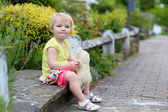 Cute little girl playing with teddy bear on the street — Stock Photo