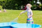 Gelukkig meisje spelen met waterslang in de tuin — Stockfoto