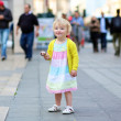 Happy little girl eating ice-cream in the center of the city — Stock Photo #47337029