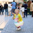 Happy little girl eating ice-cream in the center of the city — Stock Photo #47337049