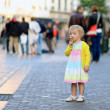Happy little girl eating ice-cream in the center of the city — Stock Photo