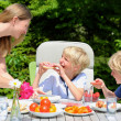 Mother and kids having lunch in the garden — Stock Photo #47337155