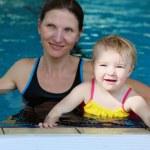 jovem mãe com filha se divertindo na piscina — Foto Stock #47337187