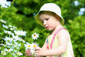 Całkiem mała dziewczynka gra w ogrodzie kwiaty stokrotki — Zdjęcie stockowe