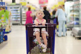Funny little girl sitting in the trolley in hypermarket — Stok fotoğraf