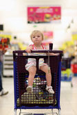 Funny little girl sitting in the trolley in hypermarket — Photo