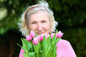 Portrait of happy senior woman with bouquet of beautiful pink tulips — Stockfoto