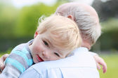 Cute little child comforting on the shoulder of grandfather — Stock Photo