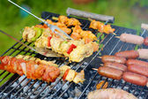 Assorted meat and vegetables on barbecue grill — Stock Photo