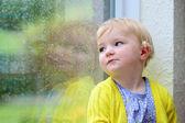 Menina bonitinha olhando pela janela chuvosa — Fotografia Stock