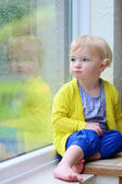 Mignonne petite fille qui regarde par la fenêtre des pluies — Photo