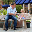 Father and daughter relaxing on the bench in urban setting — Stock Photo