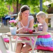 Young mother and little daughter enjoying summer drinks in outdoors cafe — Stock Photo