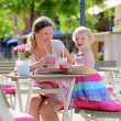 Young mother and little daughter enjoying summer drinks in outdoors cafe — Stock Photo #47846109