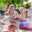 Young mother and little daughter enjoying summer drinks in outdoors cafe — Stock Photo #47846111