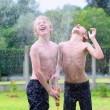 Two happy boys playing in the garden with watering hose — Stock Photo #47846167