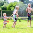 Group of happy children playing in the garden with watering hose — Stock Photo #47846211