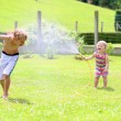 Brother and sister playing in the garden with watering hose — Stock Photo #47846263