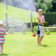 Brother and sister playing in the garden with watering hose — Stock Photo #47846273