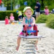 Little girl enjoying summer day at the playground bouncing on spring horse — Stock Photo #47846333