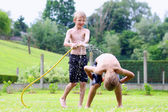 Two happy boys playing in the garden with watering hose — Stock Photo