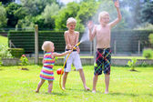 Group of happy children playing in the garden with watering hose — Stock Photo