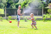 Brother and sister playing in the garden with watering hose — Stock Photo