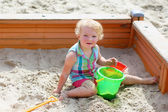 Little girl playing in sandbox — Stock Photo