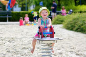 Little girl enjoying summer day at the playground bouncing on spring horse — Stock Photo