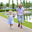 Happy kids running together along small river — Stock Photo