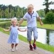 Happy kids running together along small river — Stock Photo #48734029