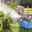 Cute little girl watering flowers in the garden using spray hose — Stock Photo #48734121
