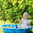 Happy little girl playing with sand in sunny garden — Stock Photo #48734161