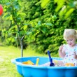 Happy little girl playing with sand in sunny garden — Stock Photo #48734163