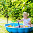 Happy little girl playing with sand in sunny garden — Stock Photo #48734169