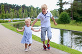 Happy kids running together along small river — Stock fotografie