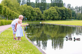 Two kids feeding ducks in little pond — Foto Stock