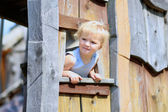 Funny little girl playing in wooden house — Stock Photo