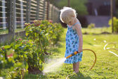 Cute little girl watering flowers in the garden using spray hose — Stock Photo