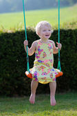 Happy little girl playing swinging in playground — Stock fotografie