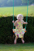 Happy little girl playing swinging in playground — Stock Photo