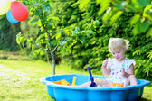 Happy little girl playing with sand in sunny garden — Foto de Stock